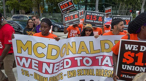 "Supporters of the ""Fight for $15"" movement march with banners and posters."